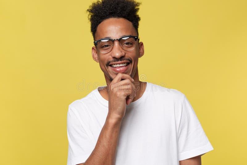 Headshot do homem de pele escura novo positivo bonito com restolho e a camisa branca vestindo do corte de cabelo na moda quando fotos de stock