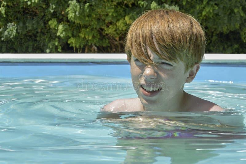 Teenage boy in swimming pool. Headshot of a ginger haired teenage boy in a swimming pool royalty free stock photo