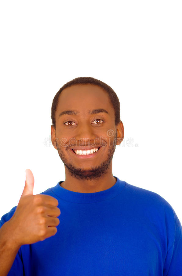 Headshot handsome man wearing strong blue colored t-shirt and giving thumb up smiling to camera royalty free stock photography