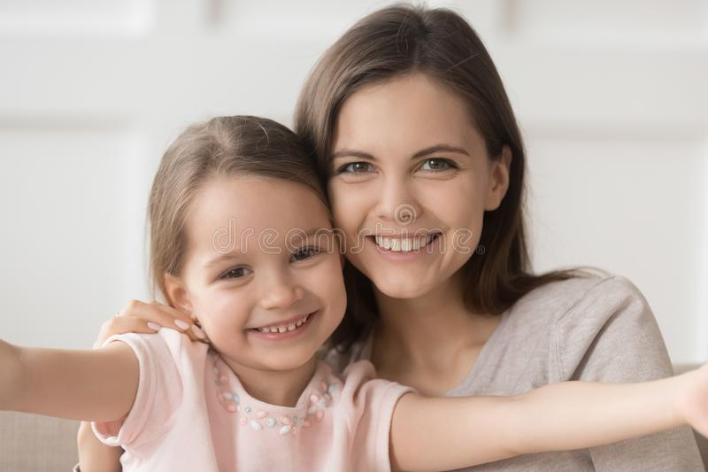 Headshot of happy family mother and kid daughter embracing bonding. Head shot of happy family single mother elder sister and little kid daughter embracing royalty free stock image