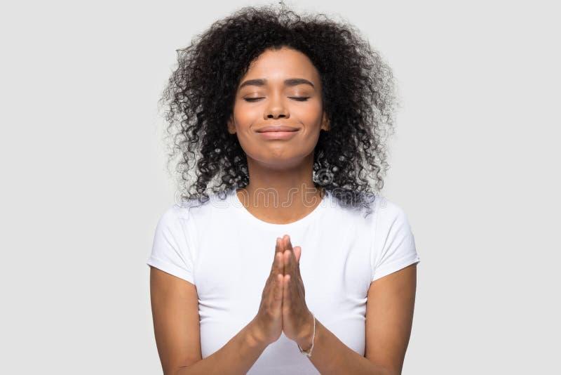 Headshot het Afrikaanse vrouwelijke het bidden stellen op grijs achtergrondstudioschot stock foto's