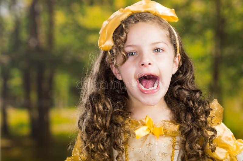 Headshot leuk meisje die mooie gele kleding met de aanpassing van hoofdband dragen, die voor camera, groen bos stellen royalty-vrije stock afbeelding