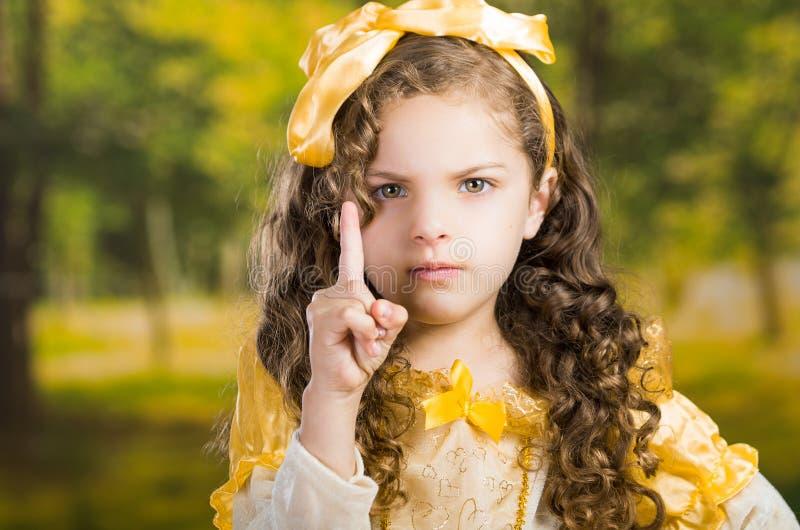 Headshot leuk meisje die mooie gele kleding met de aanpassing van hoofdband dragen, die voor camera, groen bos stellen stock foto