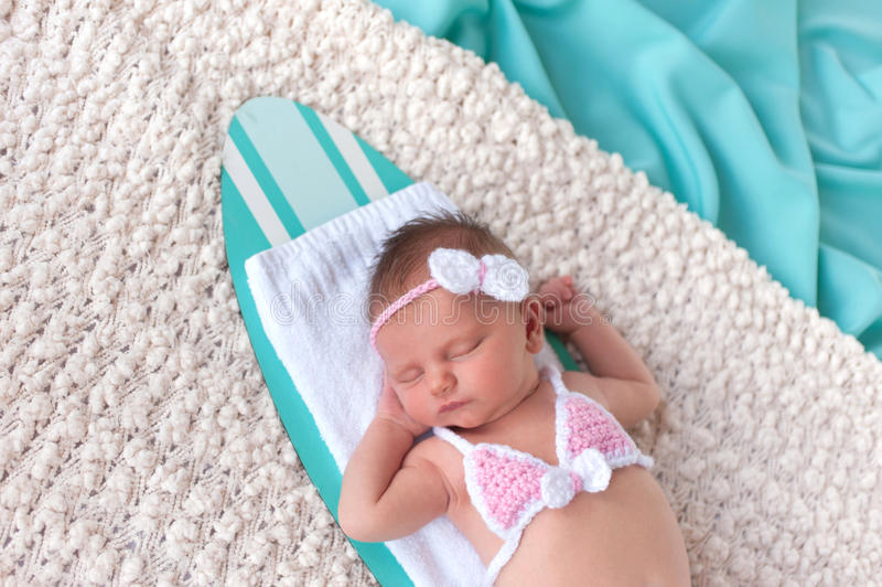 Headshot of a Newborn Baby Girl Sleeping on a Surfboard stock image