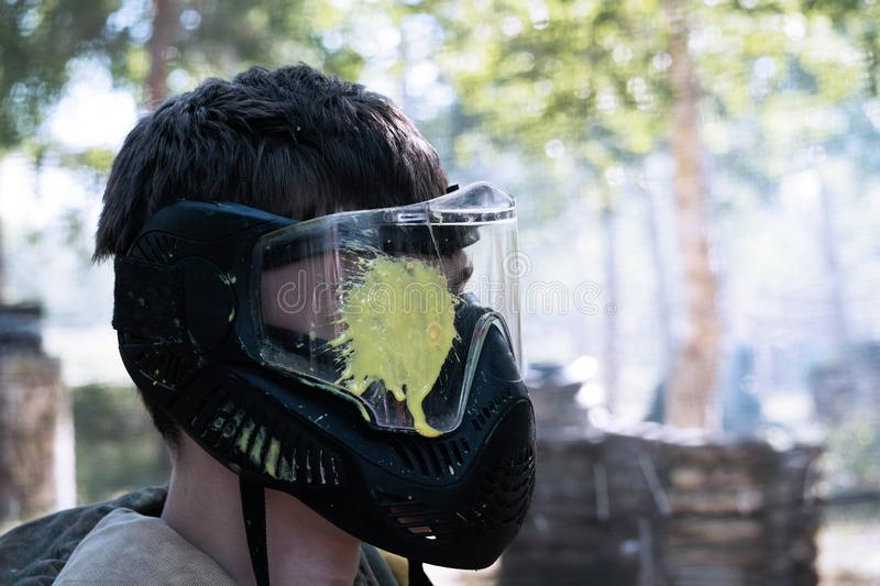 Headshot in a paintball game. The guy in a protective mask with a yellow blot on the glass at eye level. Profile of a player in a. The guy in a protective mask royalty free stock images