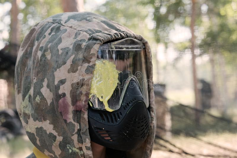 Headshot of a paintball player. The guy in the profile in a camouflage hood in a protective mask with a yellow blot on the glass. Sports lifestyle or stock photography