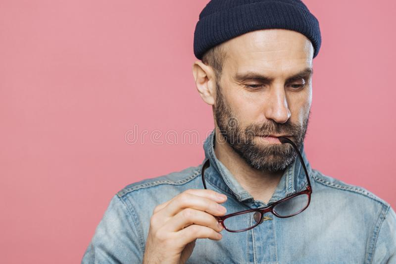 Headshot of pensive bearded man looks thoughtfully down, holds glasses, wears denim jacket and hat, isolated over pink background stock photo