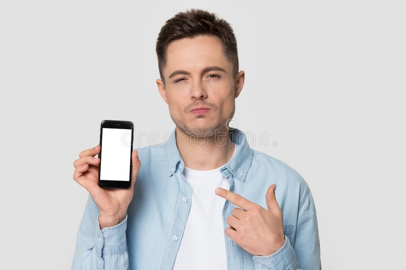 Headshot portrait confused man show smartphone with white mockup screen stock photo