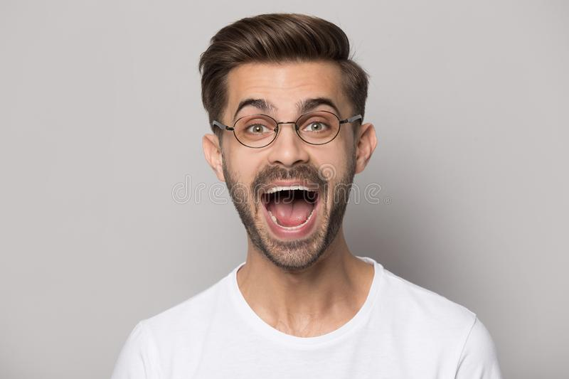 Headshot portrait funny guy wearing glasses screaming posing in studio stock photo