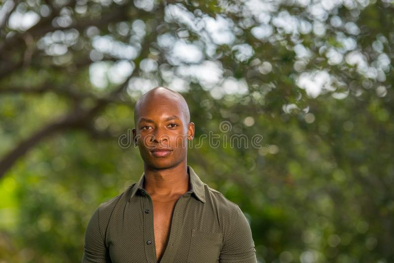 Headshot portrait of handsome African American or Jamaican male model posing at a park scene royalty free stock photo