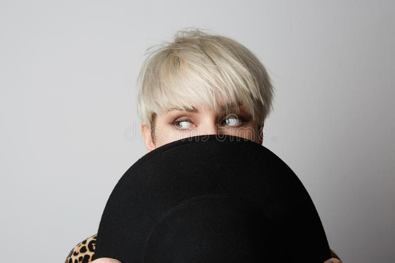 Headshot Portrait of happy blonde girl hides her face behind black hat looking asside at camera. White background royalty free stock photos