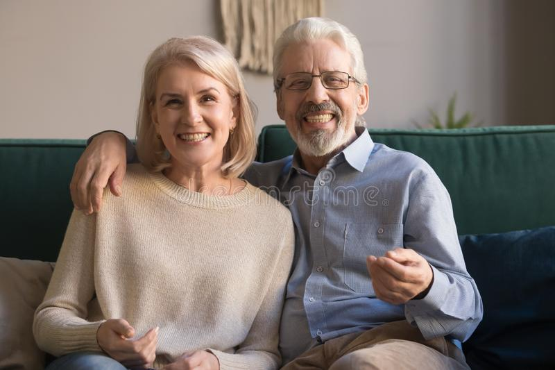 Headshot portrait of smiling mature couple sit on couch royalty free stock images