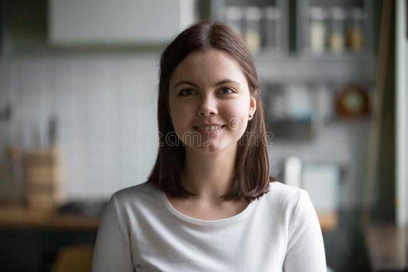 Headshot portrait of smiling millennial woman posing at home kit. Headshot portrait of smiling friendly millennial woman at home kitchen or cafe working as royalty free stock image