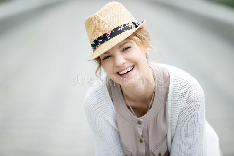 Headshot portrait of young happy woman laughing outdoors stock image