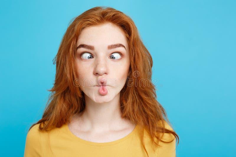 Headshot portret szczęśliwa imbirowa czerwona włosiana dziewczyna patrzeje kamerę z śmieszną twarzą Pastelowy błękitny tło kosmos obraz stock