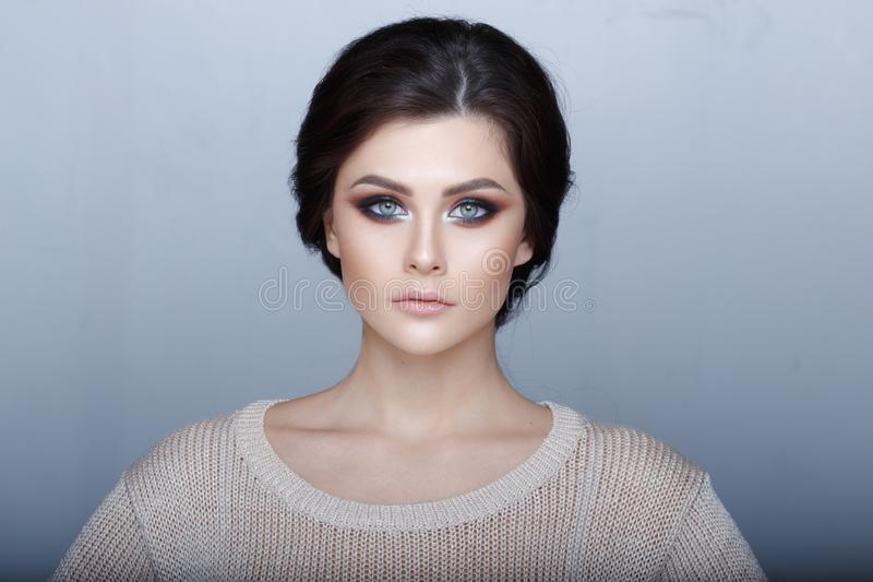 Headshot portret zmys?owa brunetki dziewczyna z zadziwiaj?cymi zielonymi oczami, doskonali? makija?, patrzeje kamer? Szary t?o zdjęcia royalty free