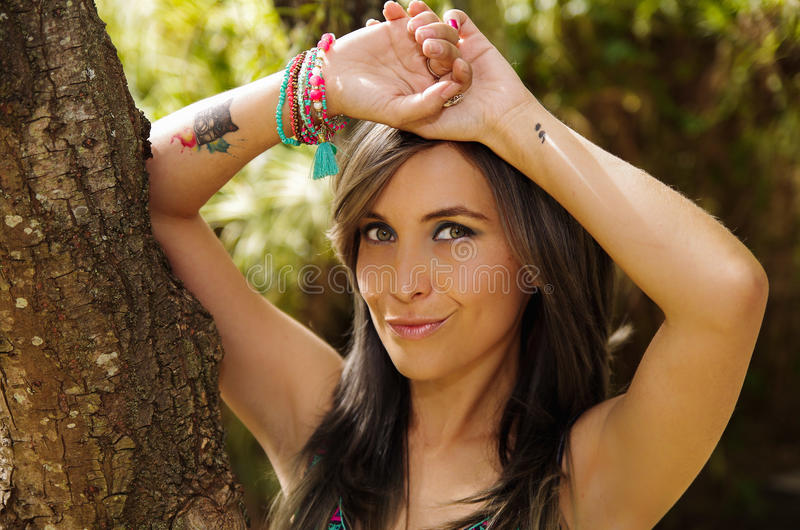 Headshot pretty brunette, standing between trees, bare skinned arms above head pose, sensually looking into camera royalty free stock photography