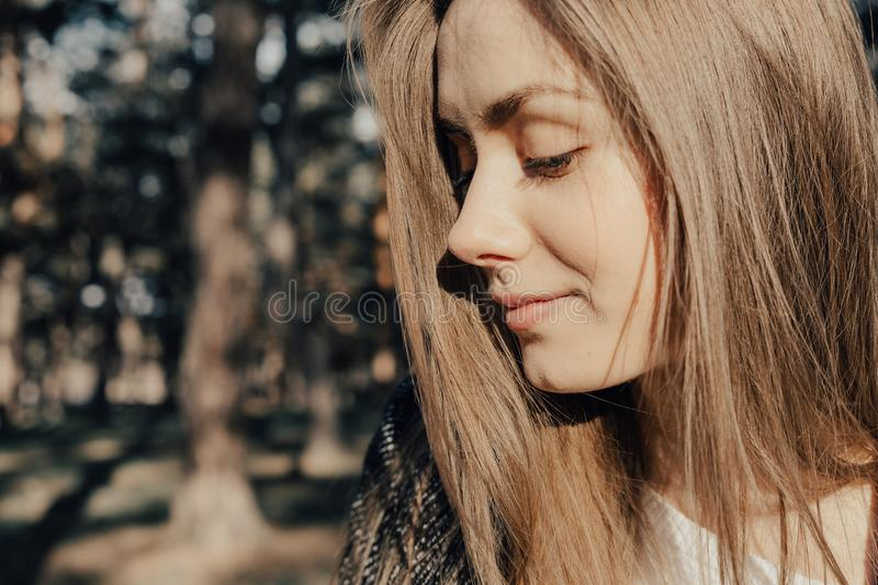 Headshot of pretty woman with blonde hair in park in warm clothes stock image