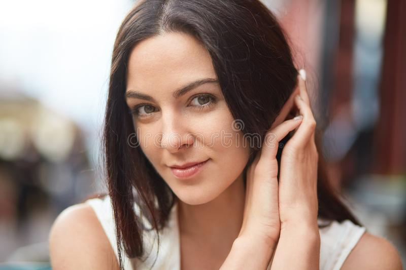 Headshot of pretty woman with dark hair, pleasant appearance, looks directly at camera, poses outdoor, expresses positive feelings royalty free stock photography