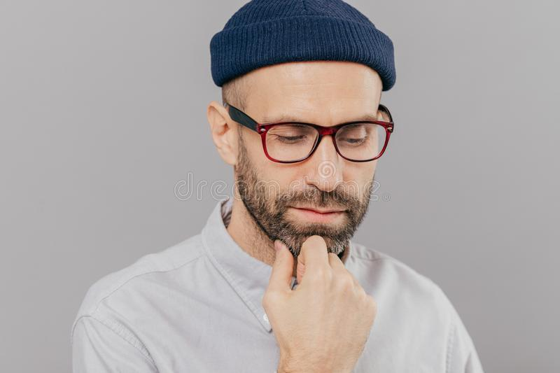 Headshot of sad lonely serious male keeps hand under chin, has dark bristle, looks down, thinks about promotion and starting new royalty free stock photos
