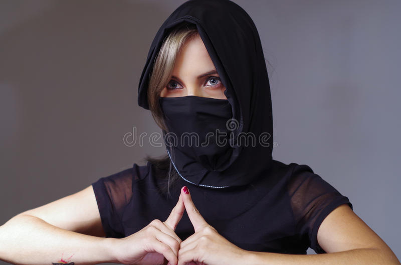 Headshot samurai woman dressed in black with matching veil covering face, resting arms on desk and touching fingertips royalty free stock images