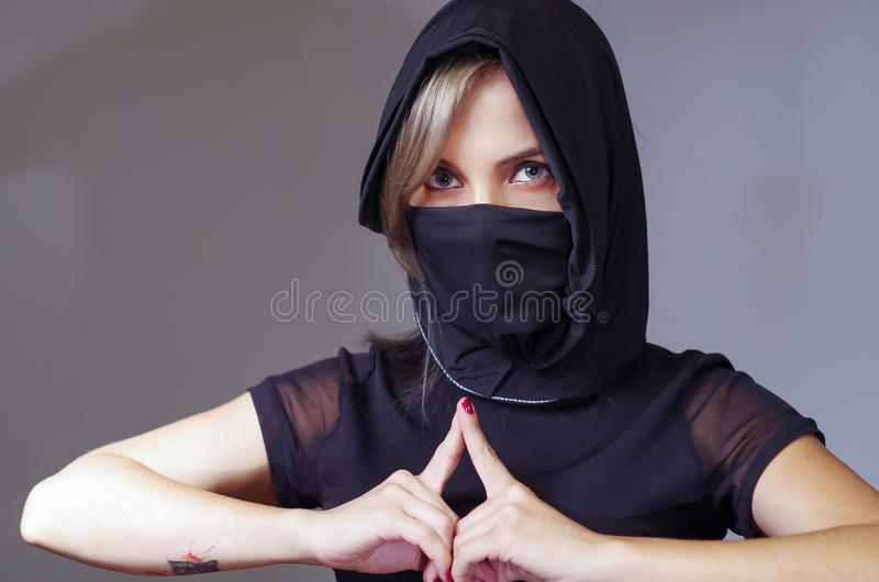 Headshot samurai woman dressed in black with matching veil covering face, resting arms on desk and touching fingertips. Against each other, facing camera, ninja royalty free stock photography