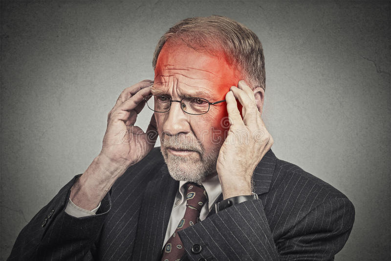 Headshot senior man suffering from headache hands on head stock photo