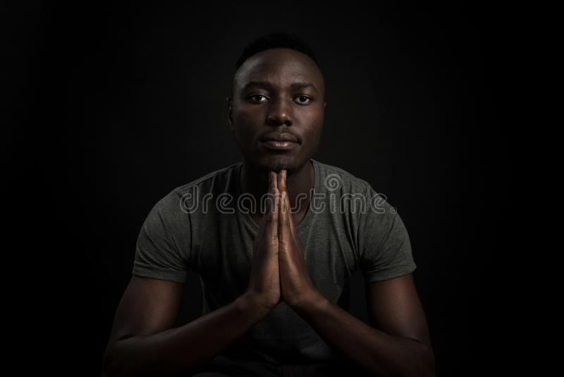Headshot of serious confident young dark-skinned male standing isolated against black studiobackground. stock photography