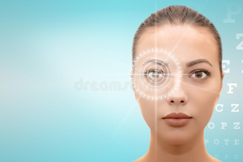 face of young beautiful woman with hi-tech laser eye surgery concept. Headshot of serious pretty woman with futuristic eye laser surgery concept  on blue and stock images