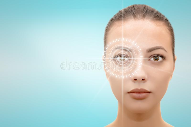 face of young beautiful woman with hi-tech laser eye surgery concept. Headshot of serious pretty woman with futuristic eye laser surgery concept  on blue and stock photos