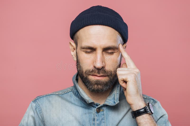 Headshot of serious thoughtful middle aged man tries to remember something in his mind, keeps fore finger on temple, keeps eyes sh royalty free stock image
