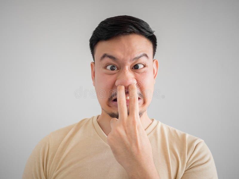 Headshot of smell something bad face of Asian man. stock photo