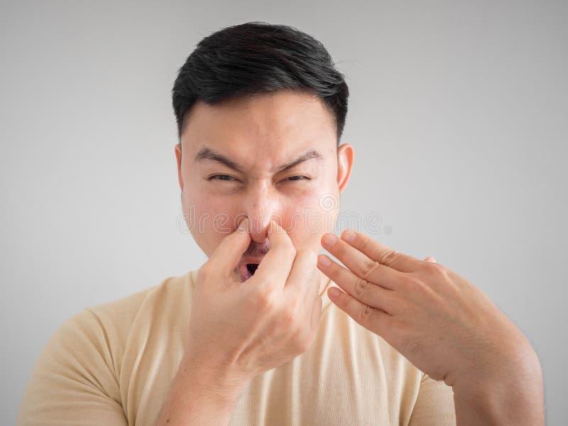 Headshot of smell something bad face of Asian man. stock photos