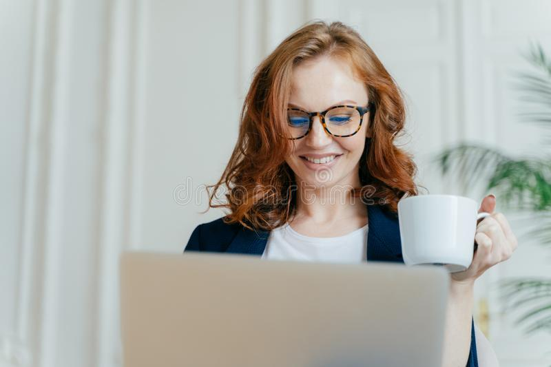 Headshot of smiling red haired female in optical glasses, enjoys hot coffee or tea, focused in laptop computer, makes purchases royalty free stock images