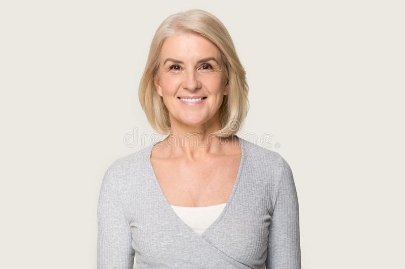 Headshot of smiling senior woman isolated on grey background stock photo