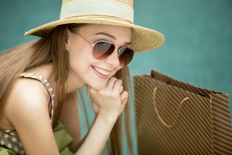Headshot of smiling woman in shopping centre. Headshot of young pretty shopper long-haired woman wearing summer hat and trendy sunglasses sitting on green royalty free stock image