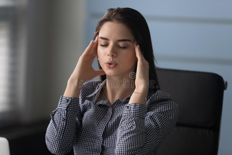 Stressed woman massaging temples, trying control work pressure at office. stock photos