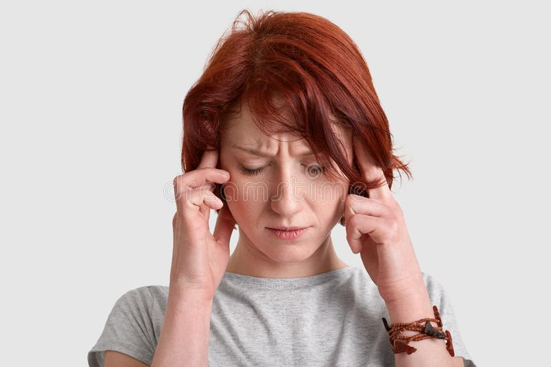 Headshot of stressful red haired young woman keeps both index fingers on temples, suffers from migraine, dressed casually, royalty free stock image