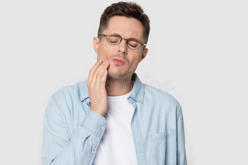 Headshot studio portrait man in glasses suffers from tooth ache royalty free stock photos