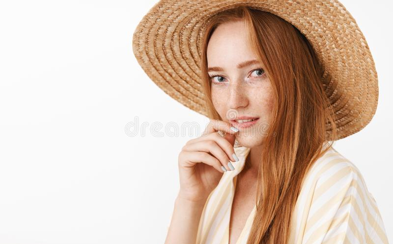 Headshot of stylish charming and flirty redhead girlfriend with freckles in straw hat and trendy yellow blouse biting royalty free stock photography