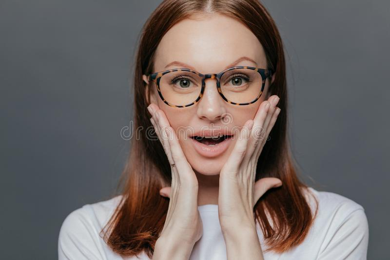 Headshot of surprised young Caucasian lady keeps both palms on her cheeks, looks with amazement, recieves unexpected news, wears royalty free stock photo