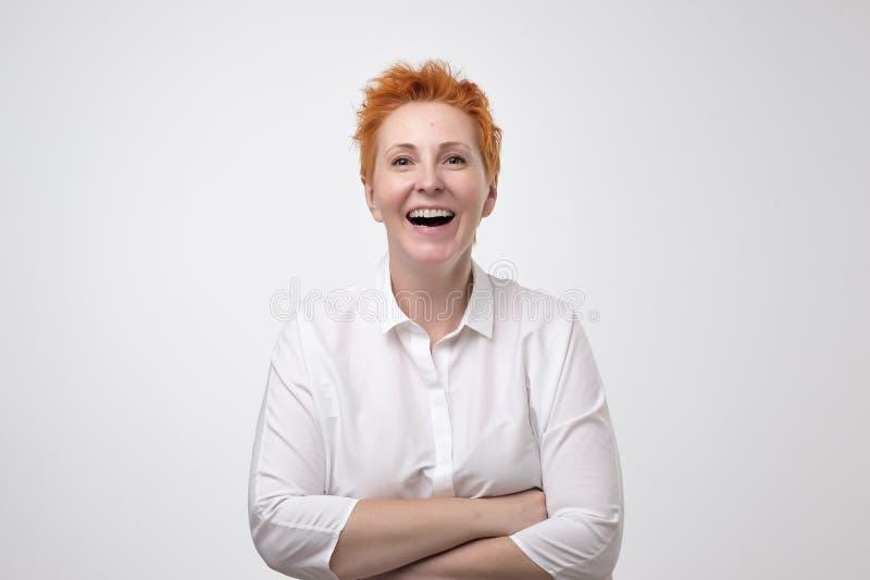 Headshot szczęśliwy emocjonalny dorośleć z czerwonym ostrzyżeniem śmia się od dna jej serce, pokazuje perfect białych zęby obrazy royalty free