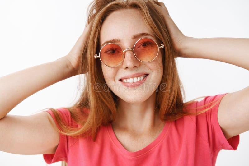 Headshot van creatief en gelukkig aantrekkelijk gembermeisje met leuke sproeten in modieuze roze zonnebril wat betreft kapsel royalty-vrije stock afbeelding