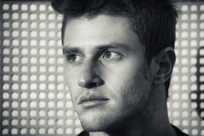Headshot van de aantrekkelijke jonge mens die aan een kant kijken stock foto