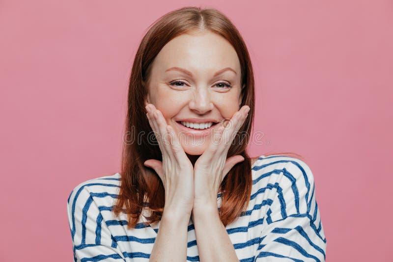 Headshot van glimlachende jonge Europese vrouw heeft omhoog maken, ruim glimlacht, houdt handen op wangen, toont haar schoonheid, stock foto's