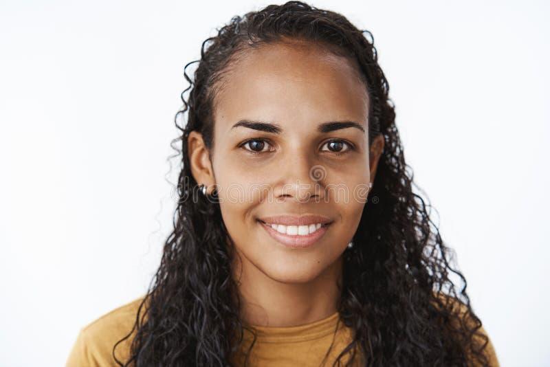 Headshot van jonge schuwe en vriendschappelijke gelukkige Afrikaans-Amerikaanse vrouw die met krullend lang haar vreugdevol bij c royalty-vrije stock fotografie
