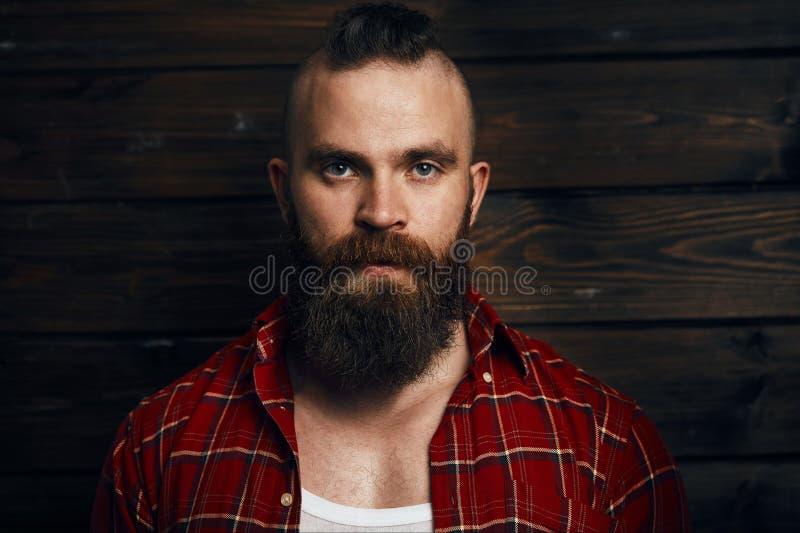 Headshot van Kaukasisch mannetje met baard en mohawk, gekleed in geruit rood overhemd royalty-vrije stock foto