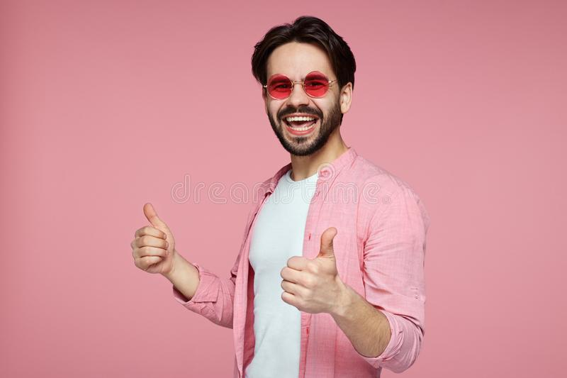 Headshot van knap jong mannetje in roze modieus overhemd en zonnebril die duim over roze achtergrond tonen stock foto's