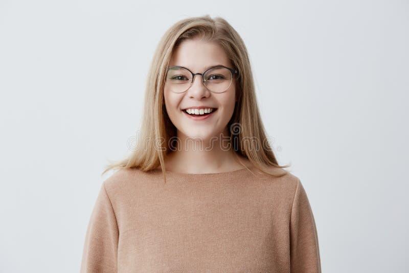 Headshot van prettig-kijkt jonge Kaukasische vrouw die oogglazen met brede glimlach dragen die haar rechte witte tanden tonen royalty-vrije stock afbeelding