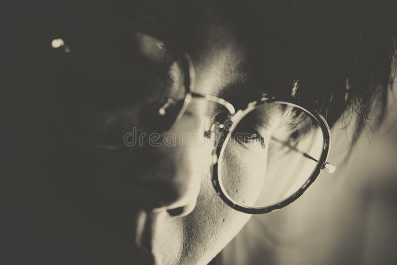 Headshot van vrouwen met ronde glazen die benedenwaarts concentrat kijken royalty-vrije stock afbeelding